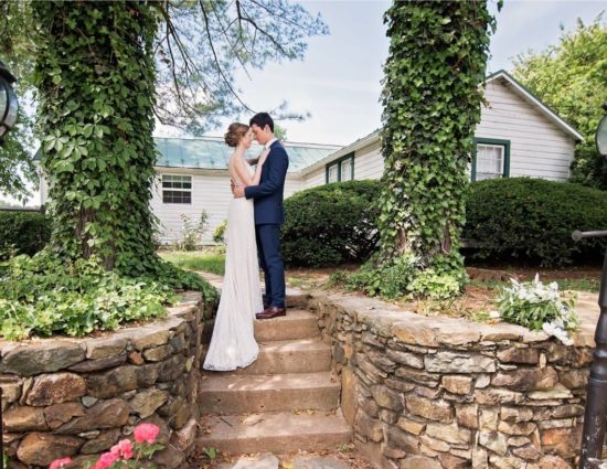 Bride in white dress and groom in dark blue suit standing on steps in front of white cottage