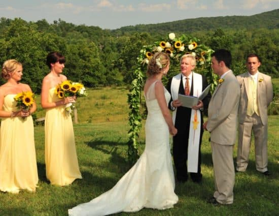 Bride in white dress and groom in light tan suit standing in front of alter with yellow and white flowers