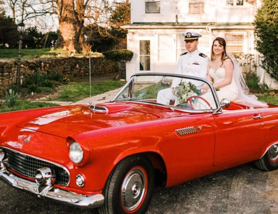 Bride in white dress and groom in white naval uniform sitting in old vintage red car
