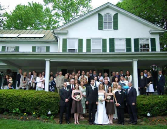 Entire wedding party with family posing in front of main house painted white with green shutters and roof