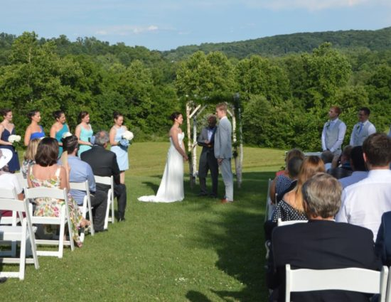 Wedding ceremony with bride in white dress and groom in light gray suit standing in front of wooden wedding alter with rolling hills in background