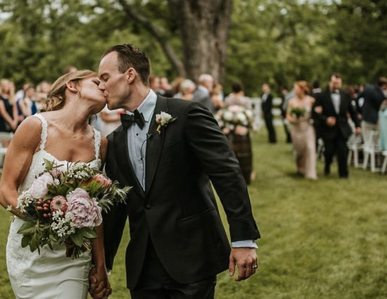Bride with white dress and groom with black suit walking down the aisle together kissing and holding hands