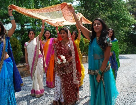 Women dressed in colorful Indian sarees with bride in the middle and scarf held over her head
