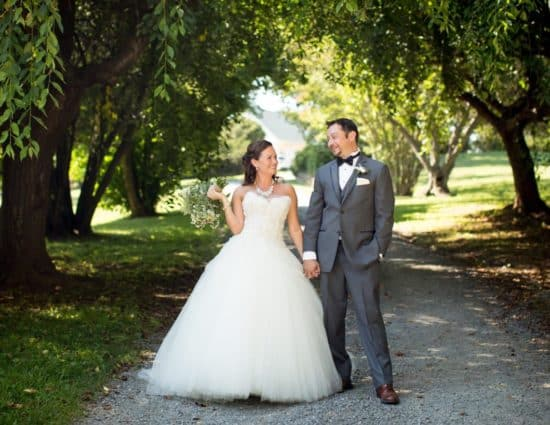 Bride in white dress and groom in gray suit standing on gravel road with green trees around them