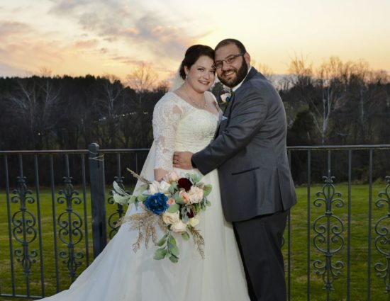 Bride in white dress and groom in gray suit standing by rod iron railing as sun sets behind