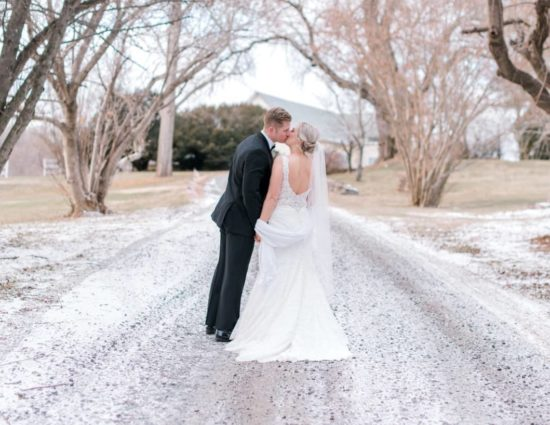 Bride in white dress and groom in black suit standing on gravel road covered in snow