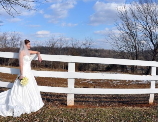 Bride in white dress standing by white fence holding bouquet of white roses