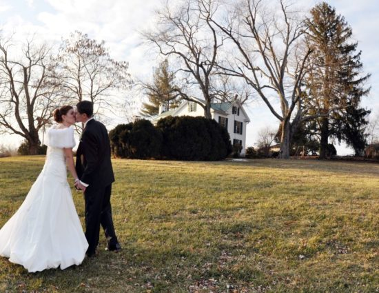 Bride in white dress and groom in black suit standing in grass on front lawn