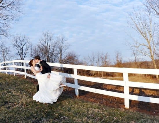 Bride in white dress and groom in black suit standing by white fence