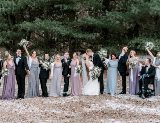 Wedding party with bridesmaids in light pink, light purple, and light gray dresses, bride in white, and groom and groomsmen in black suits