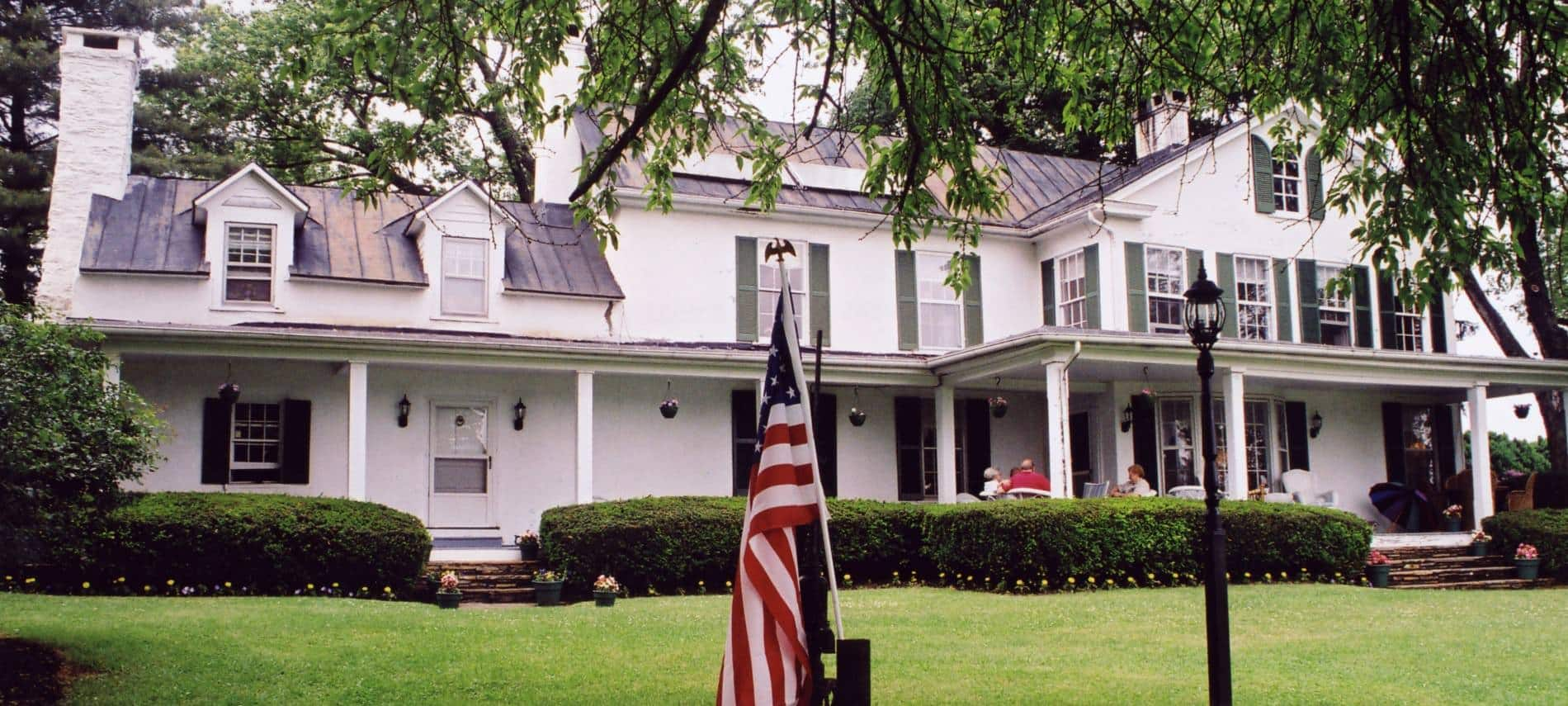 Exterior view of property painted white with dark shutters surrounded by a large green lawn and trees