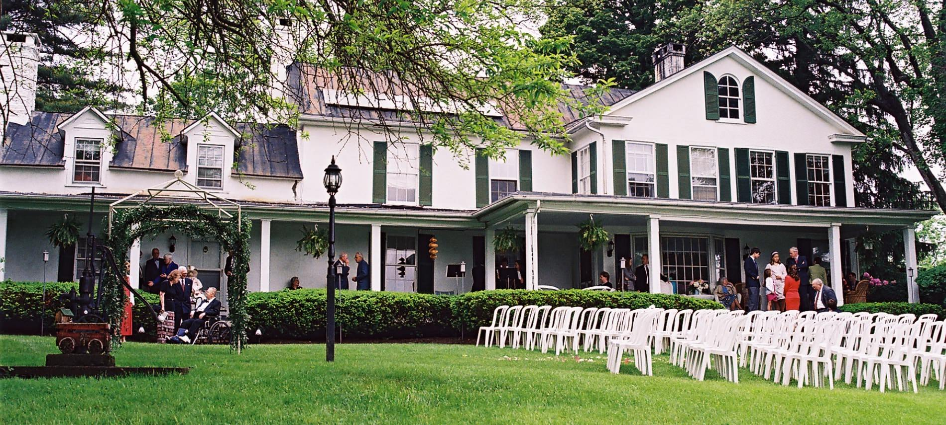 Exterior view of property painted white with dark shutters set up for a wedding with white chairs on the lawn
