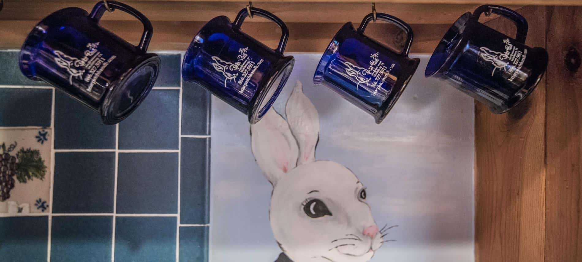 Dark blue mugs with Briar Patch logo hang on metal hooks in front of a white bunny face