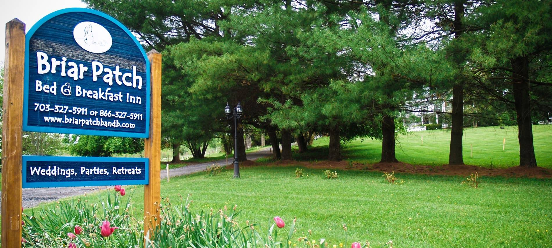 Large wooden sign painted blue with white lettering about Briar Patch Bed & Breakfast Inn surrounded by green grass, evergreen trees, and pink tulips