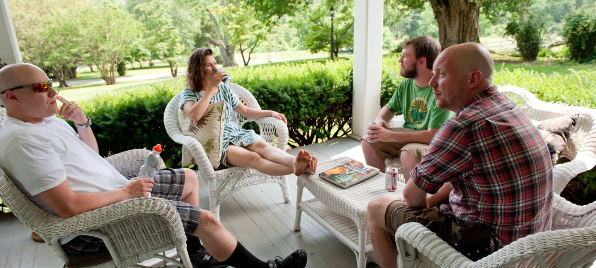 Four people sitting on white wicker patio furniture on front porch surrounded by green shrubs
