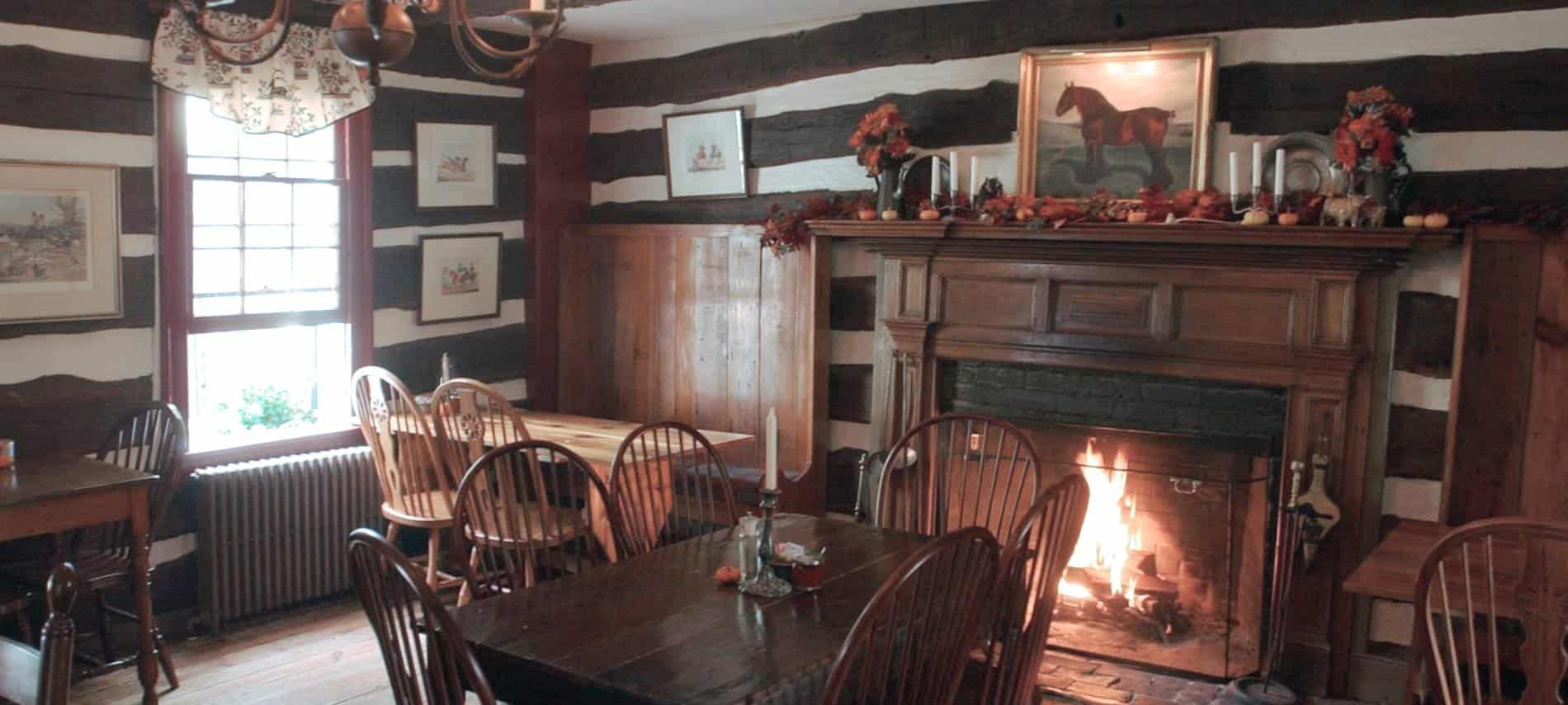 Dining area of restaurant with wooden tables and chairs next to large fireplace with dark wood mantel