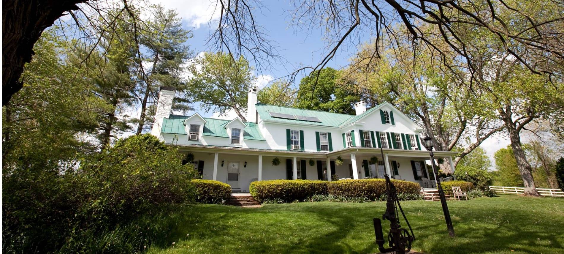 Exterior view of property painted white with dark shutters surrounded by a large green lawn, shrubs, and trees