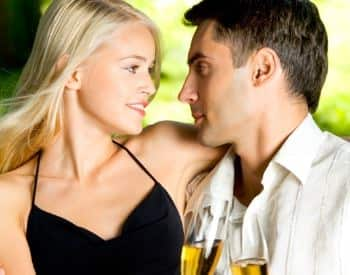 Woman with black shirt and man with white shirt looking at each other holding glasses with champagne