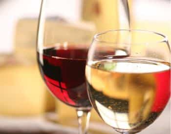 Close up view of two wine glasses, one with white wine and the other with red wine