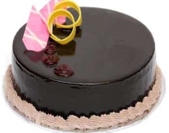 Dark chocolate cake with yellow and pink decorations on top