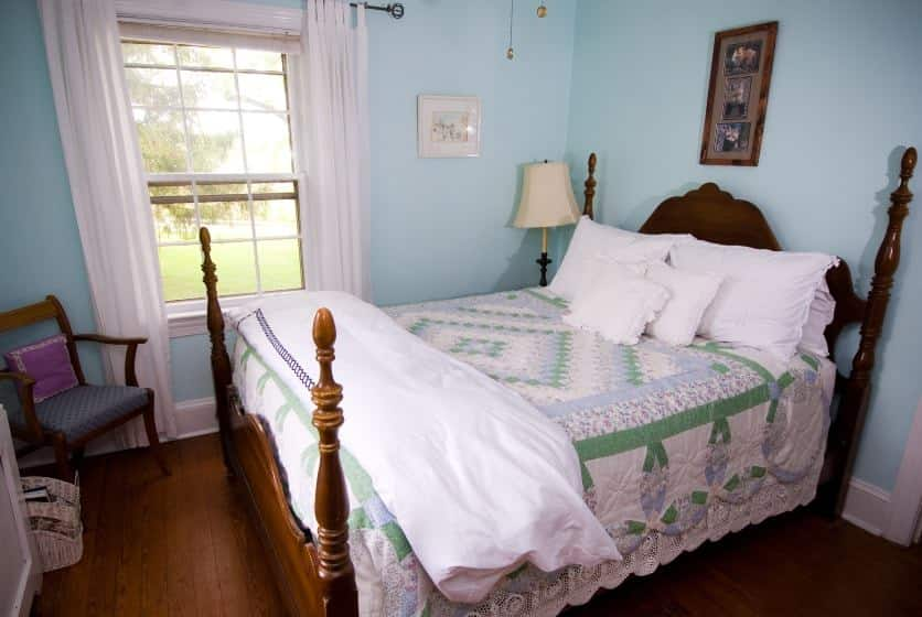 Bedroom with dark wood furntiure, green, light blue and white quilt, and light blue walls