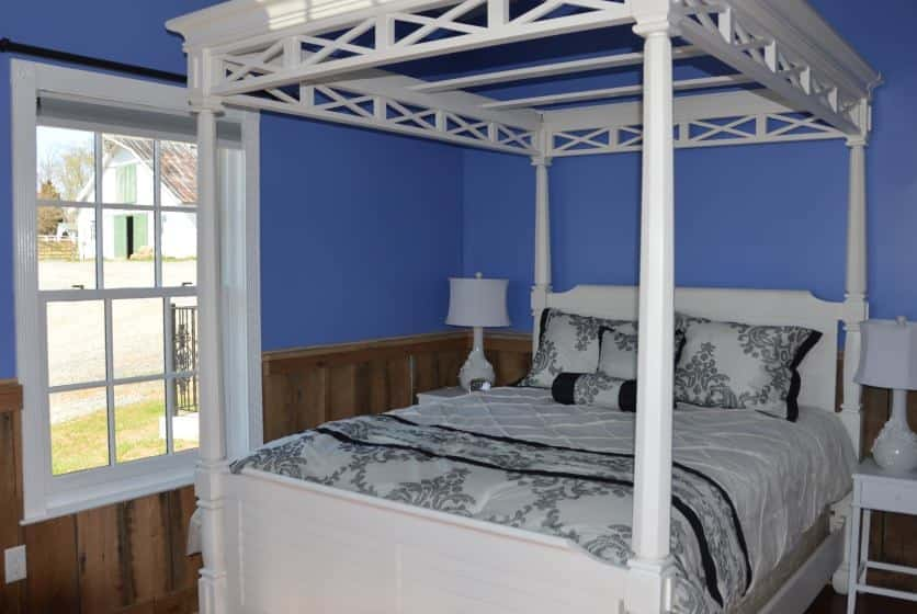 Bedroom with white wooden four-post canopy bed, white and black bedding, wood wainscoating, and blue walls