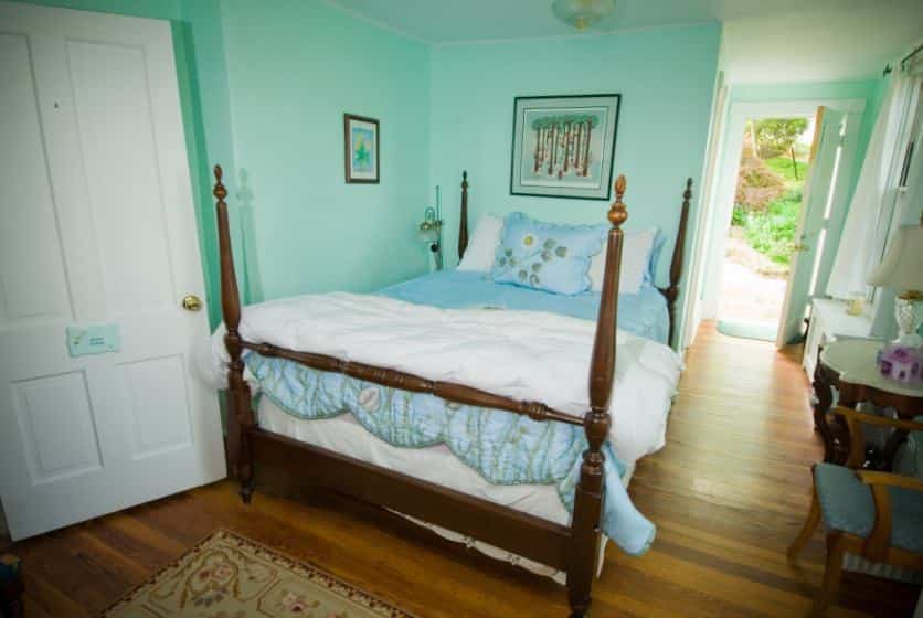 Bedroom with dark wooden furniture and four-post bed, white and blue bedding, hardwood floors, and mint colored walls
