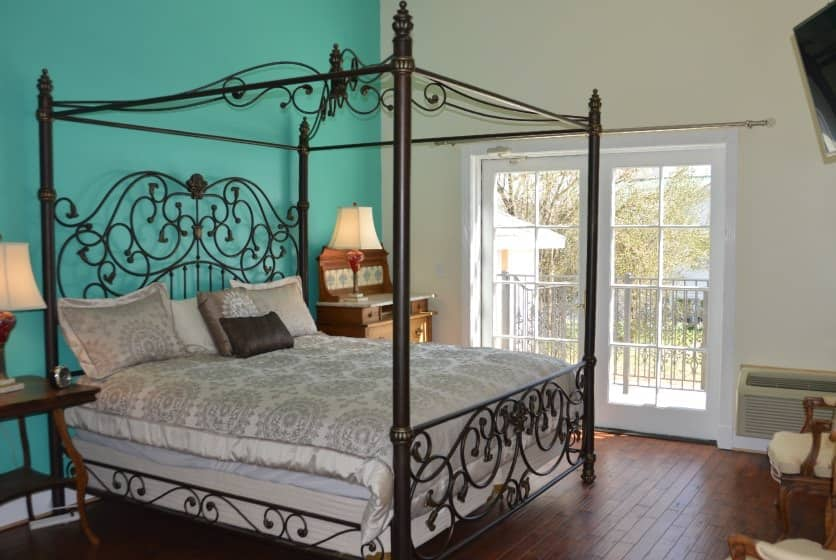 Bedroom with rod iron four-post canopy bed with light tan bedding, hardwood flooring, and a dark turquoise accent wall