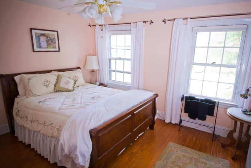 Bedroom with dark wooden sleigh bed, white and cream bedding, hardwood floors, and light pink walls