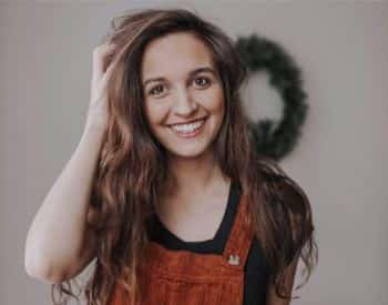 Woman with long brown hair, black shirt, and copper overalls