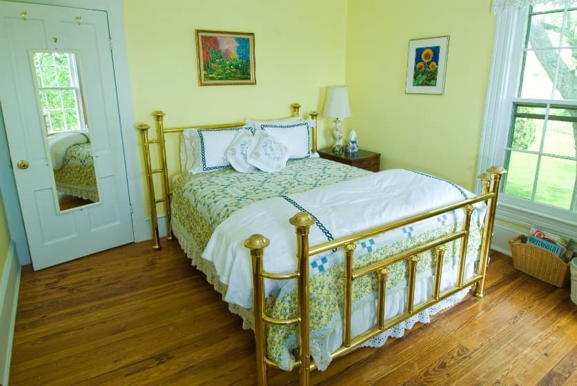 Bedroom with golden brass headboard and footboard, green, blue, and yellow floral quilt, hardwood floors, and yellow walls