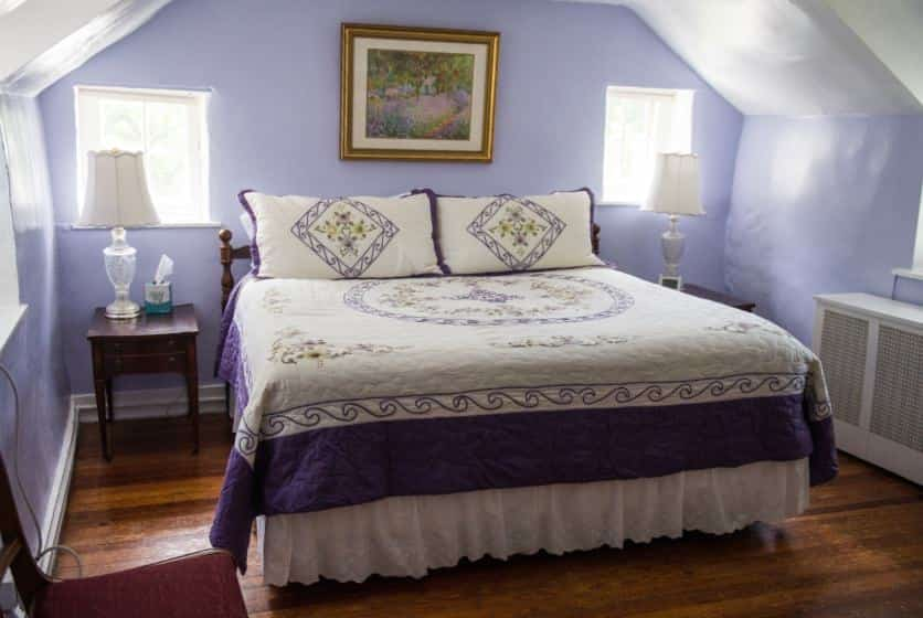 Bedroom with dark wood furniture, dark purple and white bedding, hardwood floors, and light purple walls