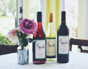 Three wine bottles, one red, one white, one rose, next to small glass vase with pink and purple flowers