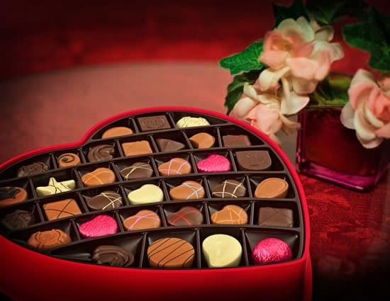 Large red valentine box filled with assorted chocolates next to pink vae with white and pink flowers