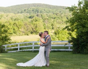 Bride in white dress and groom in gray suit kissing with white fence, green trees, and rolling hills in the background