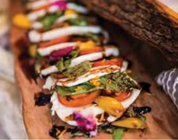 Small flour tortillas filled with grilled vegetables on a wooden plank