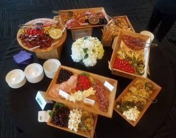Multiple wood trays with a variety of meats, cheeses, vegetables, olives, and sauces