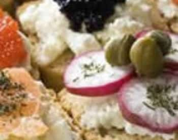 Close up view of radishes, olives, caviar, and cheese on bread