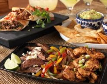 Multiple Mexican dishes on black and white serving trays