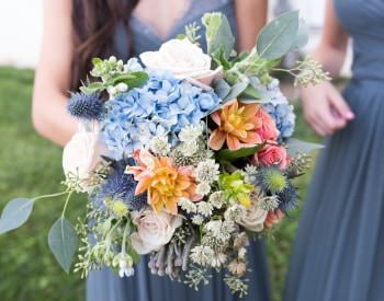 Close up view of bridal bouquet filled with a variety of blue, pink, orange, purple, and green flowers