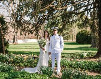 Bride with white dress and groom with white naval uniform standing on path between flowers