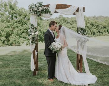 Bride in white dress with long train and groom with dark gray suit kissing under an alter draped in white fabric and white flowers